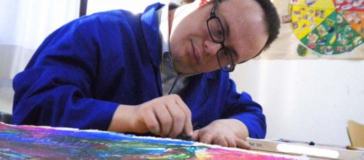Joven con síndrome de Down pintando su obra para el concurso internacional de pintura de Down Madrid